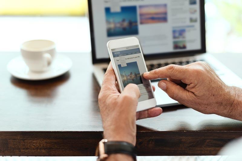 Oseba uporablja mobilni telefon za prebiranje novic